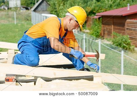 construction carpenter worker nailing wood board with hammer on roof installation work