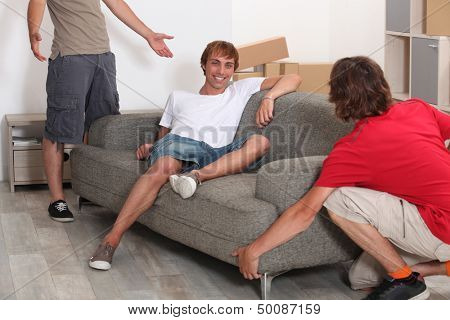 Three young men moving room