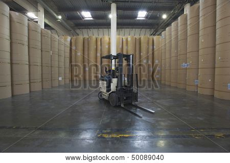 Forklift truck amid huge rolls of paper in spacious newspaper factory