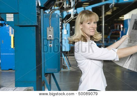 Portrait of a smiling young woman checking newspaper in the factory