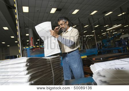 Middle aged man reading newspaper in the factory