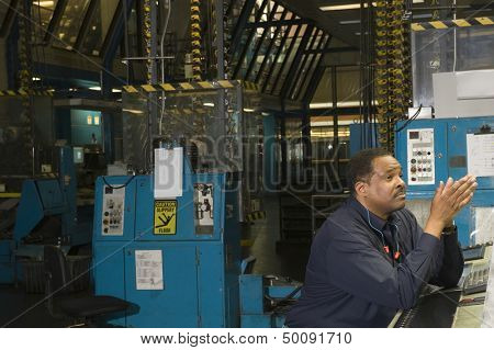 Side view of a worker in the newspaper factory