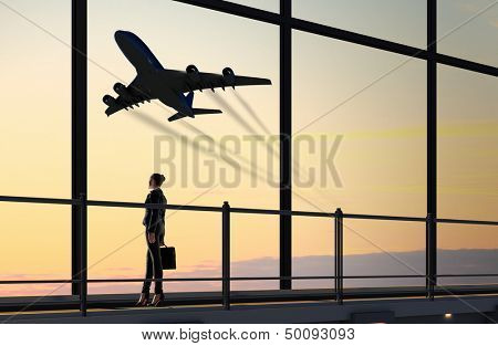 Image of businesswoman at airport looking at airplane taking off