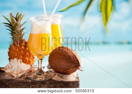 Pina colada cocktail on blue beach background