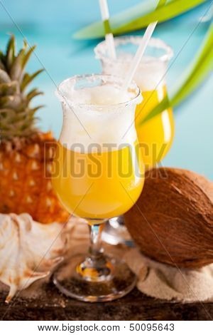 cocktail of pineapple juice, rum, liquer on table on sky background