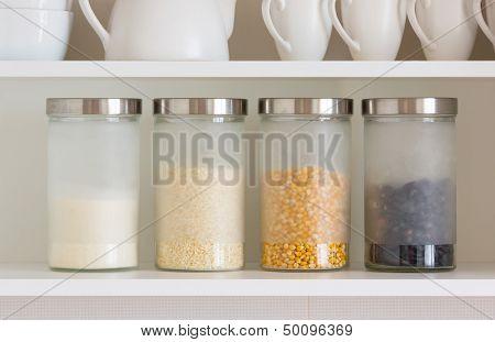 glass jars with grain on the shelf