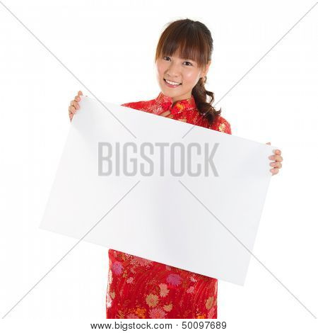 Asian woman with Chinese traditional dress cheongsam or qipao, holding blank white card. Chinese new year concept, female model isolated on white background.
