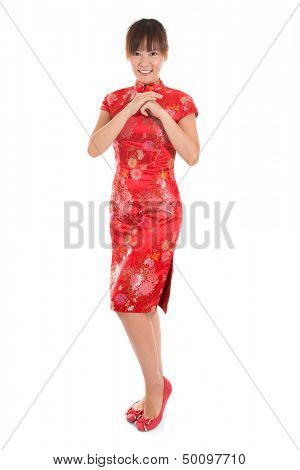 Full length Asian woman with Chinese traditional dress cheongsam or qipao respecting on Chinese New Year Festival. Female model isolated on white background.