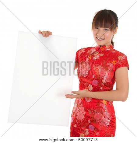 Asian woman with Chinese traditional dress cheongsam or qipao, holding blank white placard. Chinese new year concept, female model isolated on white background.