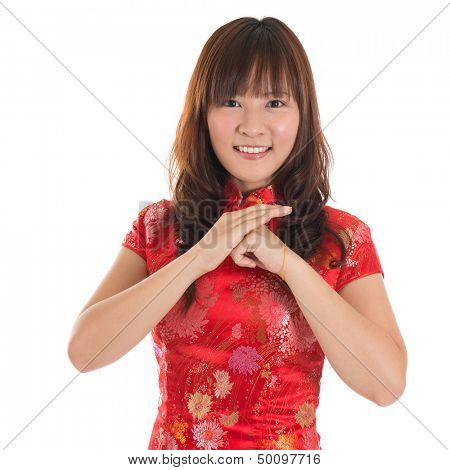 Asian woman with Chinese traditional dress cheongsam or qipao greeting. Chinese new year concept, female model isolated on white background.