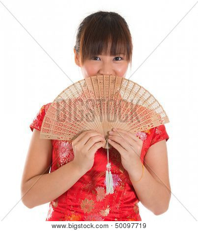 Asian woman with Chinese traditional dress cheongsam or qipao holding Chinese fan covering part of face. Chinese new year concept, female model isolated on white background.