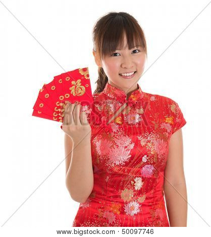 Pretty Asian girl with Chinese traditional dress cheongsam or qipao holding ang pow or red packet monetary gift. Chinese new year concept, female model isolated on white background.