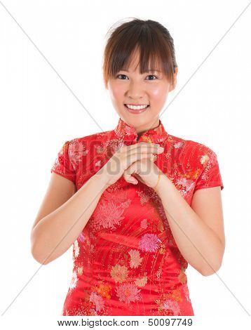 Asian woman with Chinese traditional dress cheongsam or qipao respecting on Chinese New Year Festival. Female model isolated on white background.