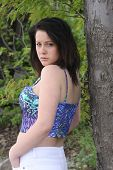 pic of halter-top  - Side view of a pretty brunette teen, in a halter top with her back near a tree trunk
