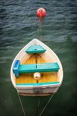 stock photo of dory  - Fiberglass dory moored in quiet water - JPG