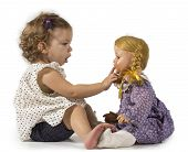 stock photo of baby doll  - Baby girl gets fascinated by a vintage doll and play with her - JPG
