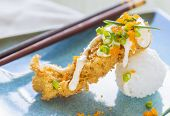 foto of masago  - Fried breaded ahi tuna resting on a ball of rice drizzled with masago mayonnaise and sprinkled with green onions and masago also known as capelin fish roe