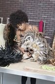 image of african mask  - African American female fashion designer working on feather mask - JPG