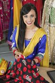 pic of dupatta  - Portrait of an Indian female dressmaker matching thread color with the cloth - JPG