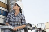 picture of take responsibility  - Mid adult woman inspecting timber truck - JPG