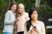 stock photo of teenagers  - Teenage Girl Being Bullied By Text Message On Mobile Phone - JPG
