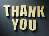 stock photo of cut torn paper  - The word Thank you in cut out paper letters on paper background - JPG