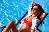 picture of sunbathing woman  - young beautiful  woman in bikini and sunglasses by the pool take sunbath - JPG