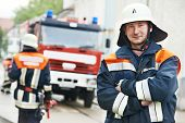 stock photo of fire brigade  - Fireman in uniform in front of fire engine or fire truck during training - JPG