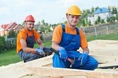image of work crew  - construction carpenters workers crew on roof installation work - JPG