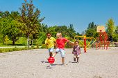stock photo of playground  - Excited kids running with a ball on the playground - JPG