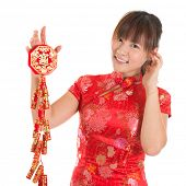 image of chinese crackers  - Pretty Asian woman with Chinese traditional dress cheongsam or qipao holding fire crackers - JPG