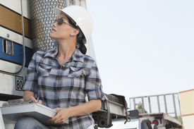 picture of logging truck  - Mid adult woman inspecting timber truck - JPG