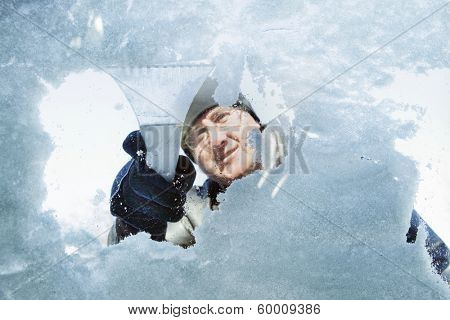 Man scraping snow and ice from car window