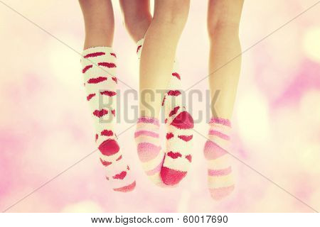 Four crossed legs with colorful socks - friendship or love concept