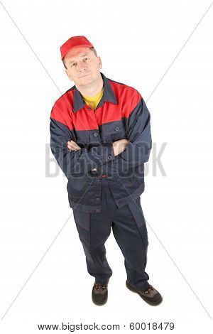 Man in working clothes with crossed arms.