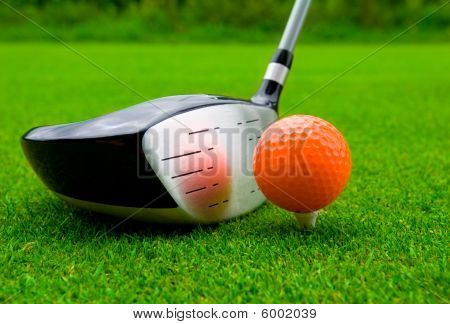 A golf driver with an orange ball