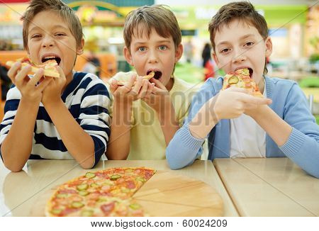 Three little boys eating pizza at cafe