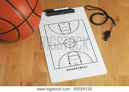 A Basketball With Coach's Clipboard And Whistle On A Wooden Gymnasium Floor