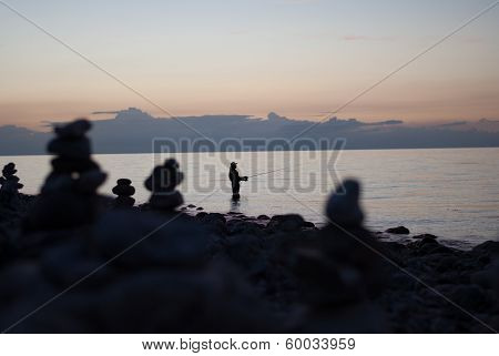 Fisherman At A Beach At Dusk