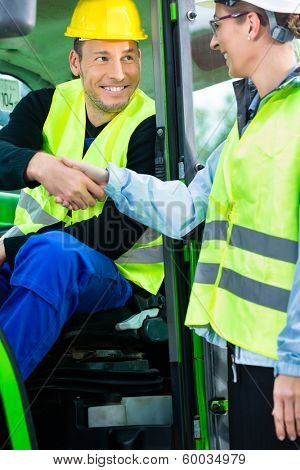 Construction worker in construction machinery hand shake with engineer to welcome on construction site