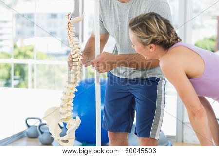 Fitness trainer showing model of spinal cord to woman at gym