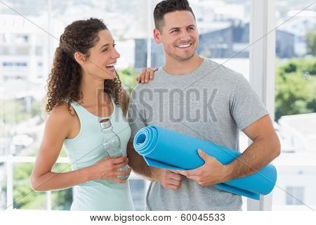 Cheerful couple holding water bottle and exercise mat in exercise room