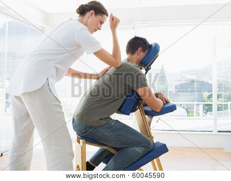 Side view of man receiving massage from physiotherapist in hospital