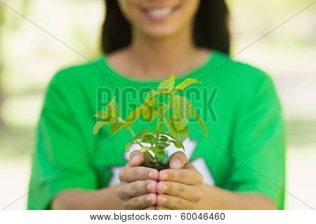 Close-up mid section of a woman in green recycling t-shirt holding young plant at the park