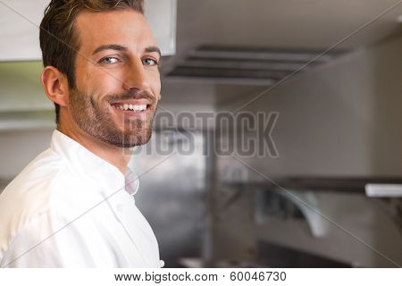Cheerful young chef looking at camera in a commercial kitchen