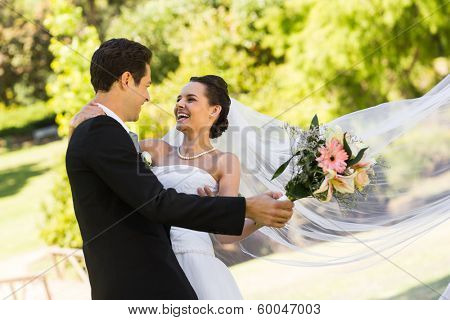 View of a cheerful newlywed couple dancing in the park