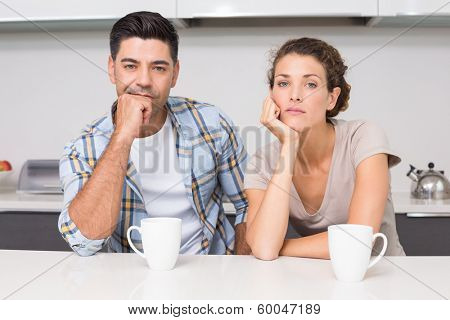 Fed up couple having coffee looking at camera at home in kitchen