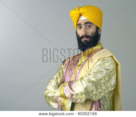 Portrait of Indian sikh man with bushy beard standing against a grey background