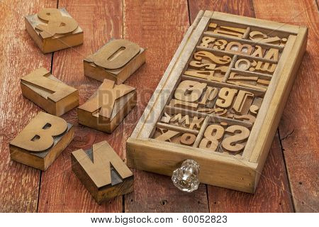 letterpress wood type blocks in a typesetter drawer against rustic red barn wood