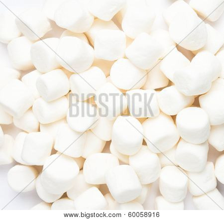 A Pile Of Small White Puffy Marshmallows On White Background. Close Up